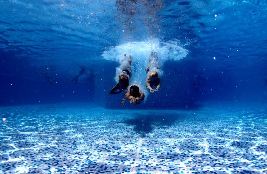 3 personnes qui plongent dans une piscine